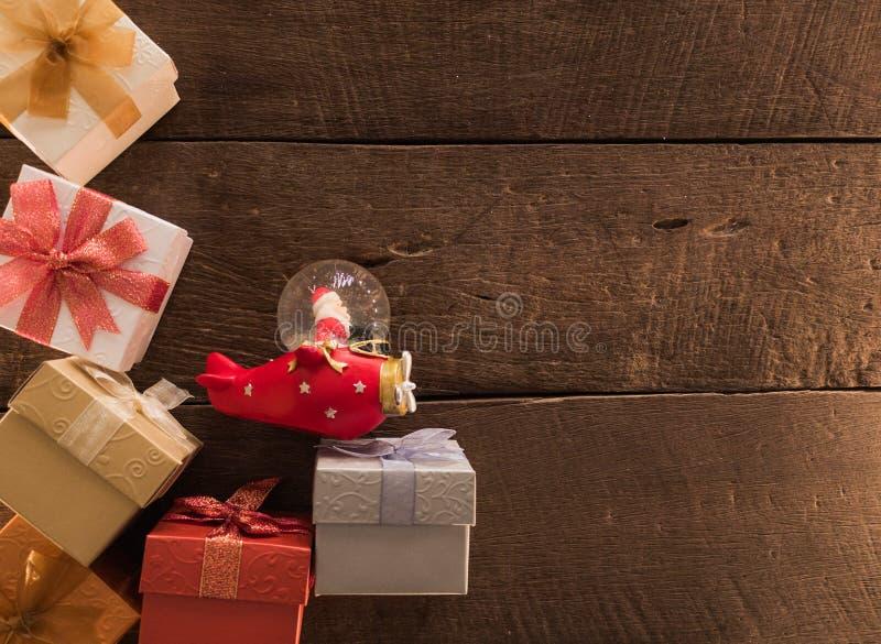 Ramen av jul för gåvaaskar och det santa jordklotet på träskrivbordbakgrund och tömmer utrymme för text Bästa sikt med kopierings arkivfoton