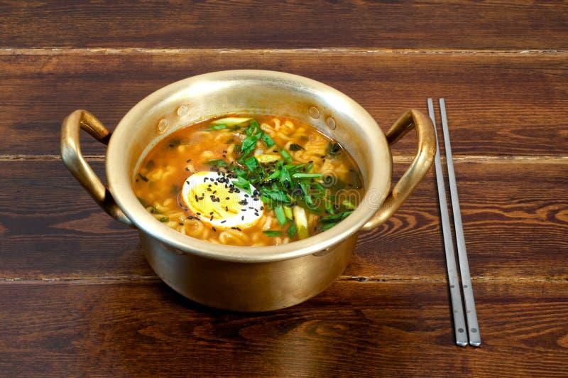 Ramen in golden pan. Korean ramen with egg and green onion on golden pan stock photography