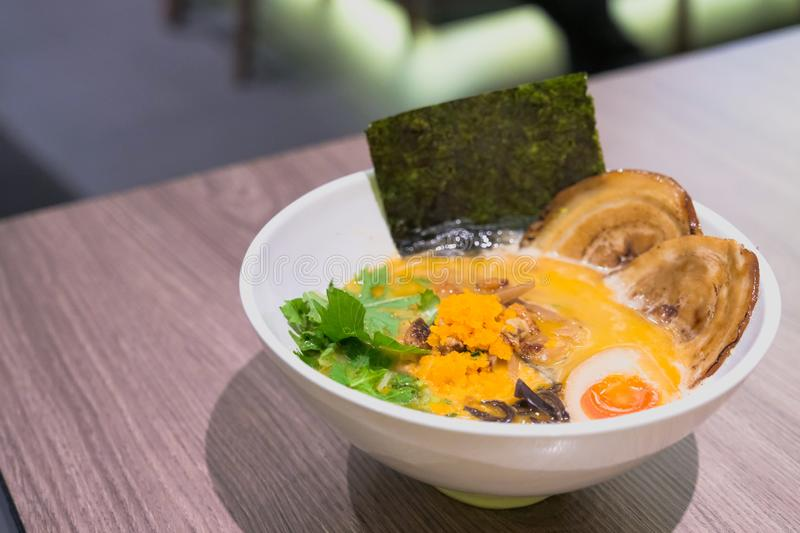 Ramen or Japanese noodles topping with Chashu or boiling pork, onions and scallions in clear soup served in a bowl. On brown wooden table royalty free stock photography