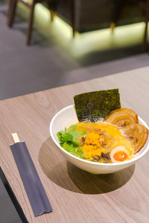 Ramen or Japanese noodles topping with Chashu or boiling pork, onions and scallions in clear soup served in a bowl. On brown wooden table stock images