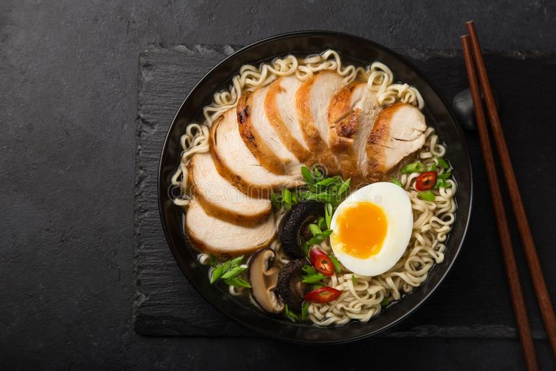 ramen noodle soup with chicken, shiitake mushroms and egg in black bowl royalty free stock images