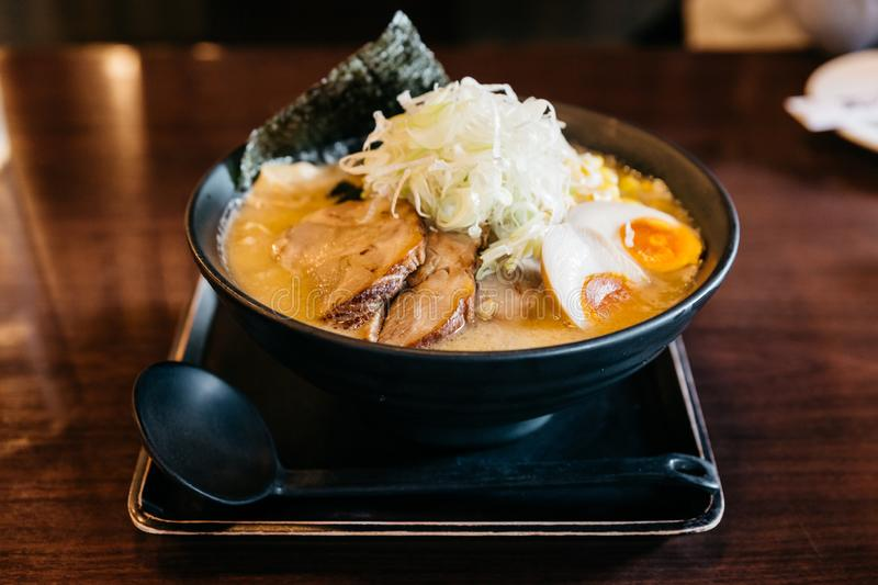 Ramen Pork Bone Soup Tonkotsu Ramen with Chashu Pork, Scallion, Sprout, Corn, Dried Seaweed and boiled egg served in black bowl stock images