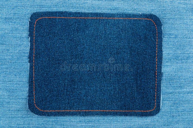 Ramen som göras av grov bomullstvill med att sy för guling, är på ljus jeans royaltyfri fotografi
