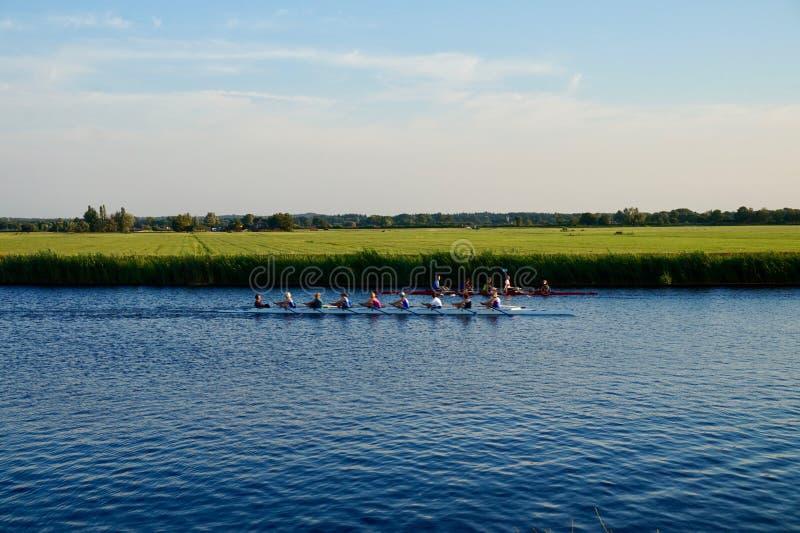 Rameurs sur un canal néerlandais avec l'herbe et les terres cultivables scéniques photo stock