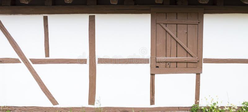 Ramhus med korsvirkes- vita vägg- och bruntstrålar royaltyfri bild