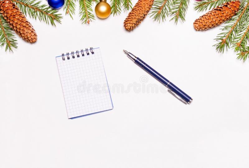 Rami dell'abete di Natale, i giocattoli del nuovo anno e coni in mezzo alla struttura il taccuino e la penna per registrare gli o immagine stock