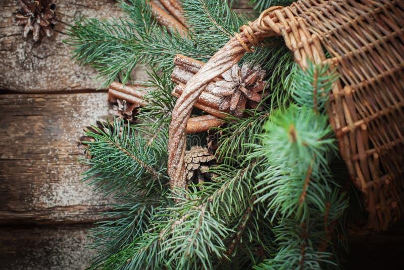 Rami dell'albero, della cannella e delle pigne di abete blu sparsi dal canestro rurale Vista superiore immagine stock