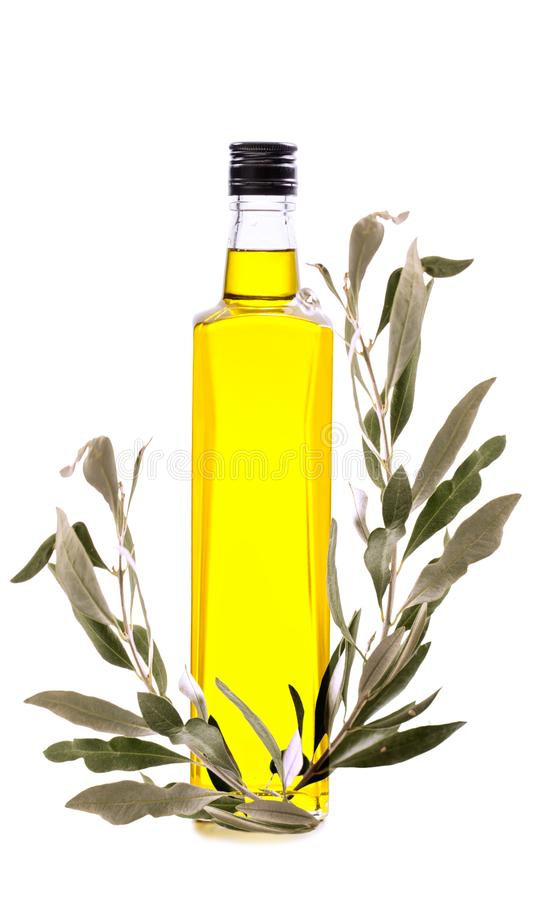 Ramifichi con le olive verdi e una bottiglia di olio d'oliva isolata su w immagini stock