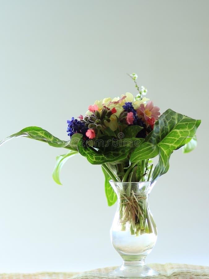 Ramillete de las flores coloridas exhibidas en un pequeño florero de cristal foto de archivo
