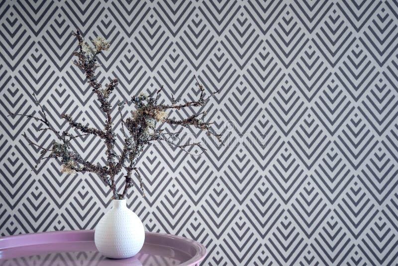 Ramitas cubiertas de musgo en un florero en fondo geométrico del papel pintado fotografía de archivo
