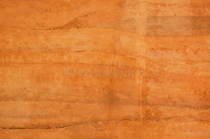 Rammed earth wall with different shades of orange soil. Rammed earth wall texture with different shades of orange soil stock image
