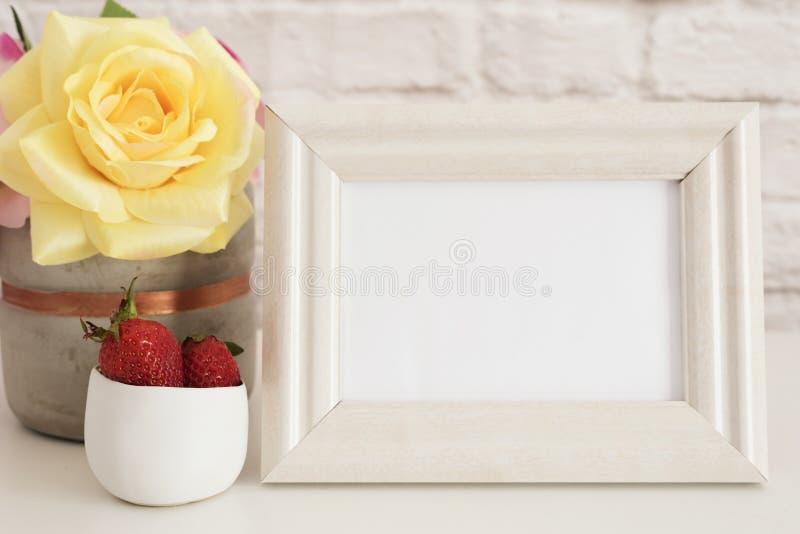 Rammodell Vit ramåtlöje upp Kräm- bildram, vas med rosa rosor, jordgubbar i guld- bunke Produktrammodell Wal royaltyfria foton