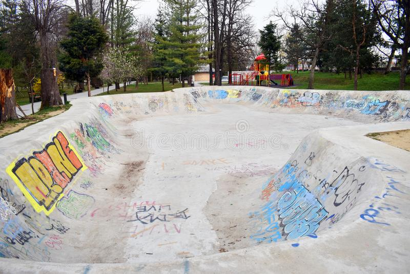 Ramnicu瓦尔恰,罗马尼亚- 02 04 2019 - 与街道画的滑冰的冰鞋公园skatepark设计滑板踩滑板的空的混凝土 库存图片