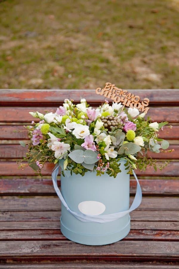 Ramo blando hermoso de flores en caja azul en backgr de madera fotografía de archivo libre de regalías