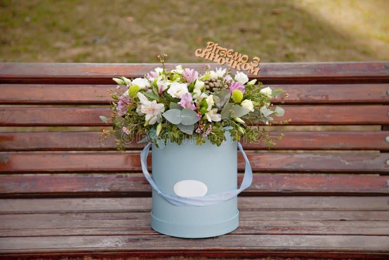 Ramo blando hermoso de flores en caja azul en backgr de madera fotos de archivo