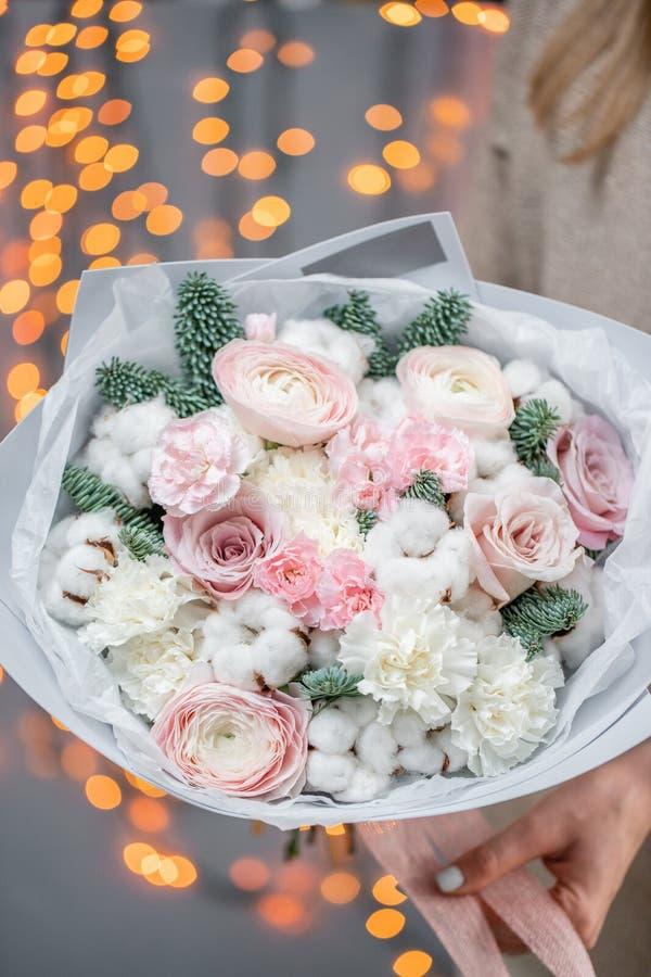Ramo brillante del invierno de flores mezcladas con algodón, las ramas Nobilis del pino y el ranúnculo Manojo floral con el persa fotos de archivo