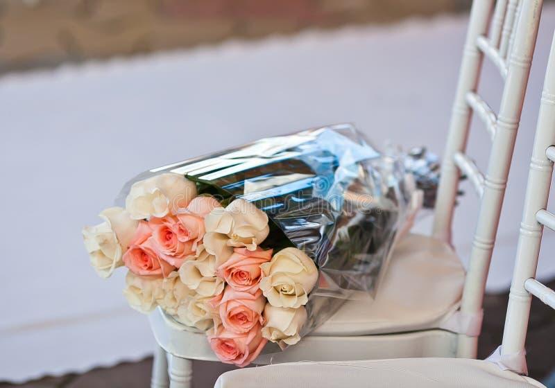 Ramo color de rosa del regalo en envoltura plástica en silla en la alfombra de la boda imagen de archivo libre de regalías