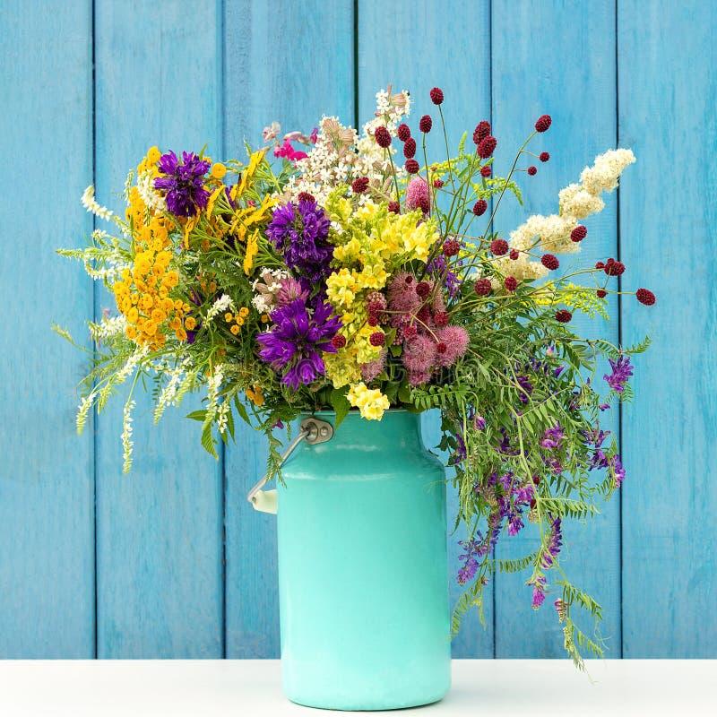 Ramo colorido brillante de flores salvajes en florero de la lata del starm en los tableros de madera azules del fondo Plantilla p imagen de archivo libre de regalías