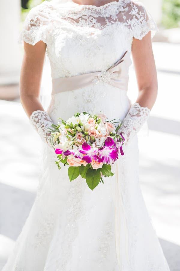 Ramo colorido en manos del ` s de la novia, fondo blanco de la boda foto de archivo libre de regalías