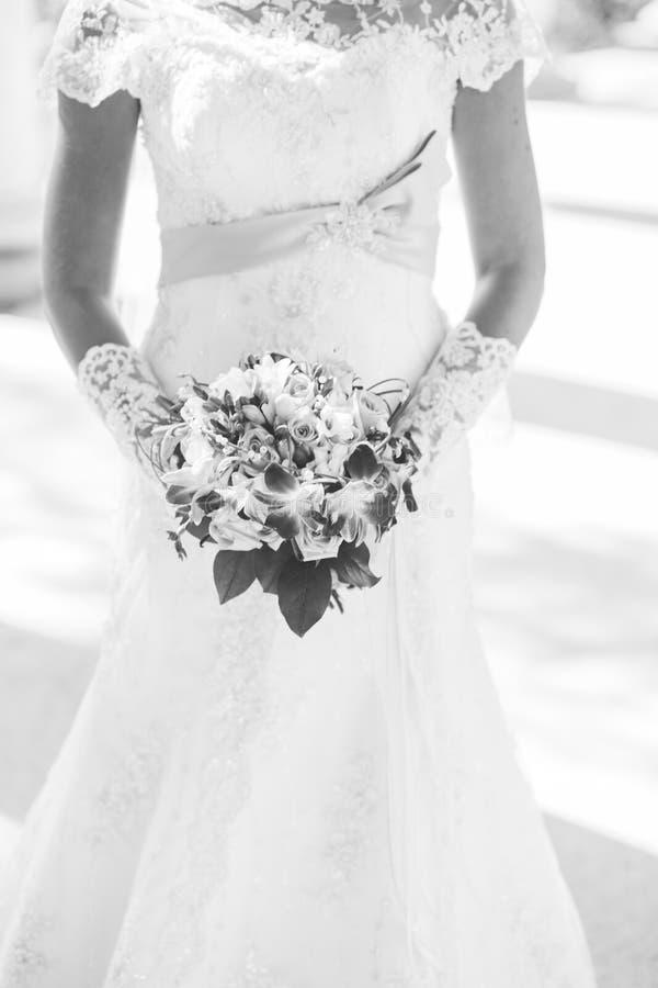 Ramo colorido en manos del ` s de la novia, fondo blanco de la boda imagenes de archivo