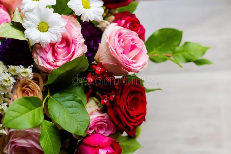 Ramo colorido hermoso de flores de rosas, de manzanillas y del verdor en la tabla imágenes de archivo libres de regalías