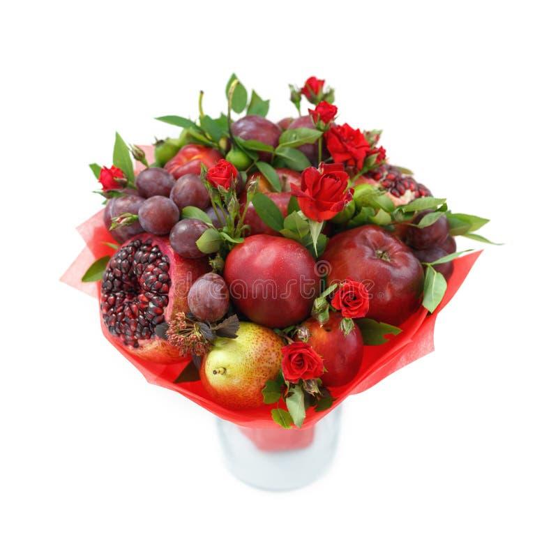 Ramo comestible que consiste en la granada, manzanas, ciruelos y las rosas del escarlata que se colocan en un florero aislado en  fotos de archivo libres de regalías