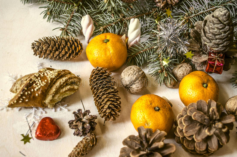 Ramo conífero com ouropel, mandarino, pastelarias, cones e porcas imagens de stock