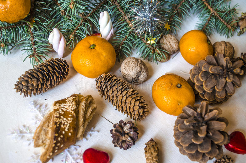 Ramo conífero com tangerinas, cones do pinho com doces fotografia de stock royalty free