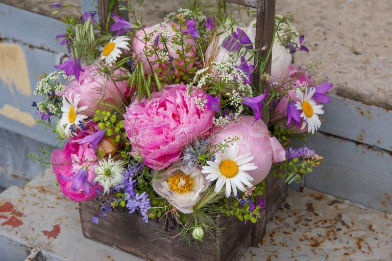 Ramo con la peonía rosada, la manzanilla y las plantas verdes en cesta de madera foto de archivo