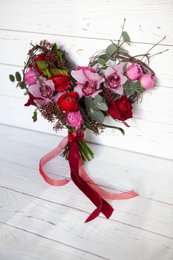 Ramo creativo inusual de flores en la forma del corazón en el fondo de madera blanco r fotografía de archivo libre de regalías