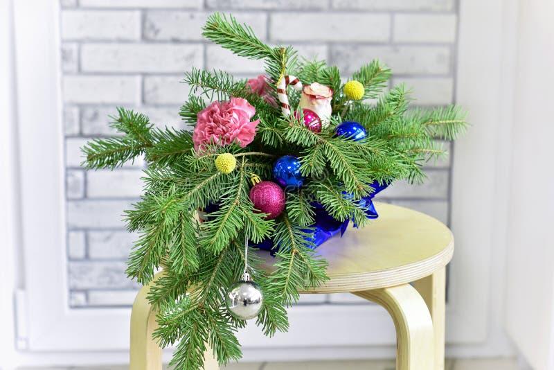 Ramo de árbol de navidad con las decoraciones de la Navidad y claveles y rosas vivos en fondo ligero fotos de archivo