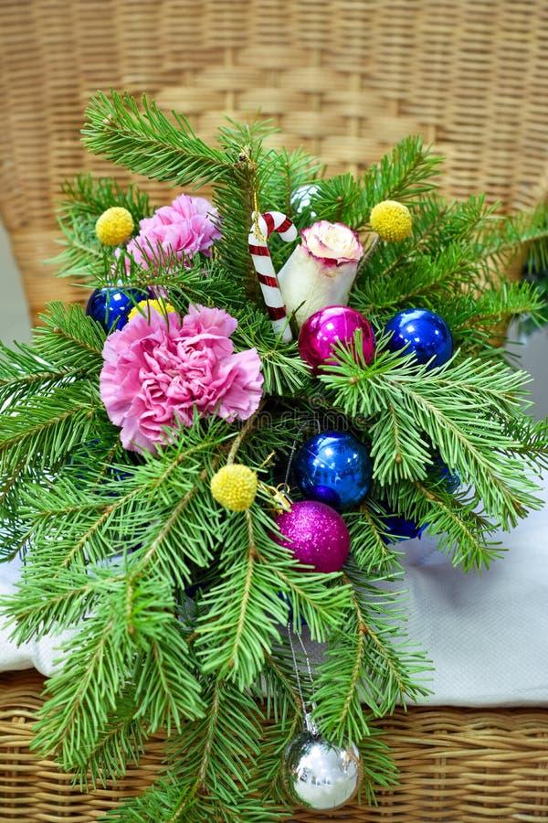 Ramo de árbol de navidad con las decoraciones de la Navidad y las flores preciosas En una silla de mimbre imagen de archivo libre de regalías