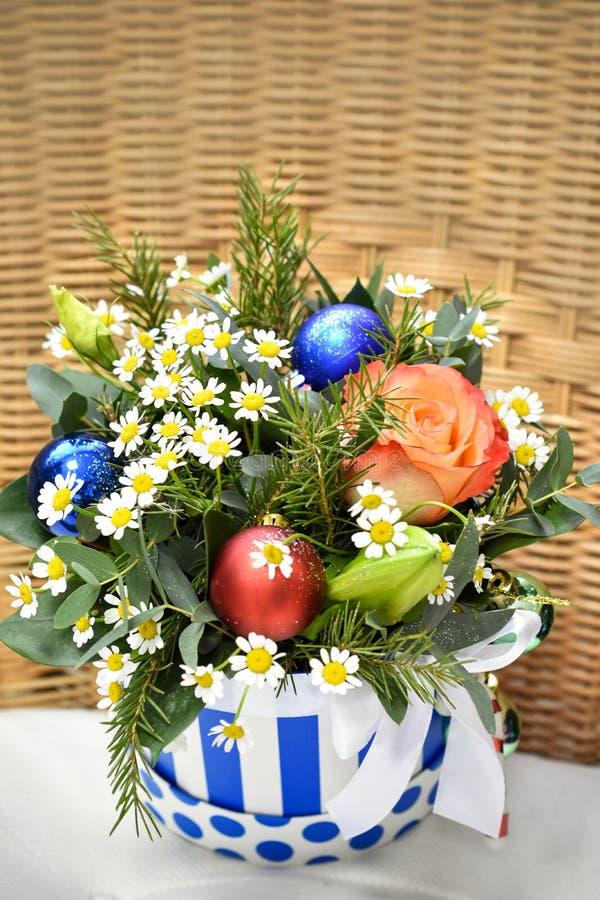 Ramo de árbol de navidad con las decoraciones de la Navidad y las rosas vivas En una silla de mimbre en una caja rayada fotografía de archivo libre de regalías