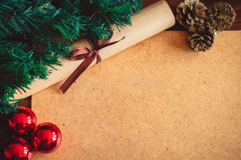 Ramo de árvore do Natal, três bolas vermelhas, cones e papel do rolo com uma curva no fundo do xmas do espaço da cópia da tabela fotos de stock