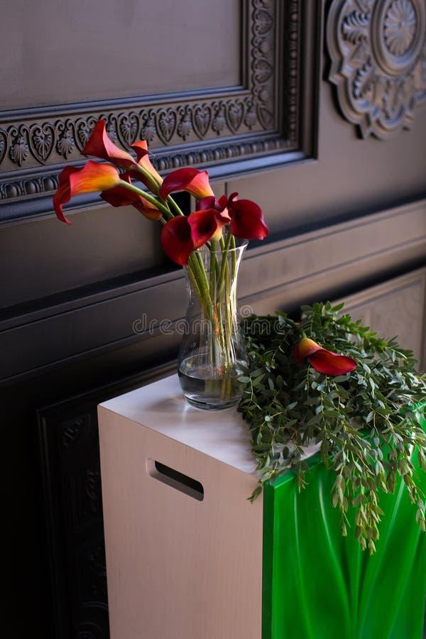 Ramo de calas rojas en un florero de cristal con una granada y un eucalipto imagenes de archivo