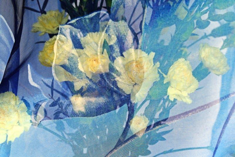 Ramo de claveles amarillos debajo de una bufanda azul fotografía de archivo