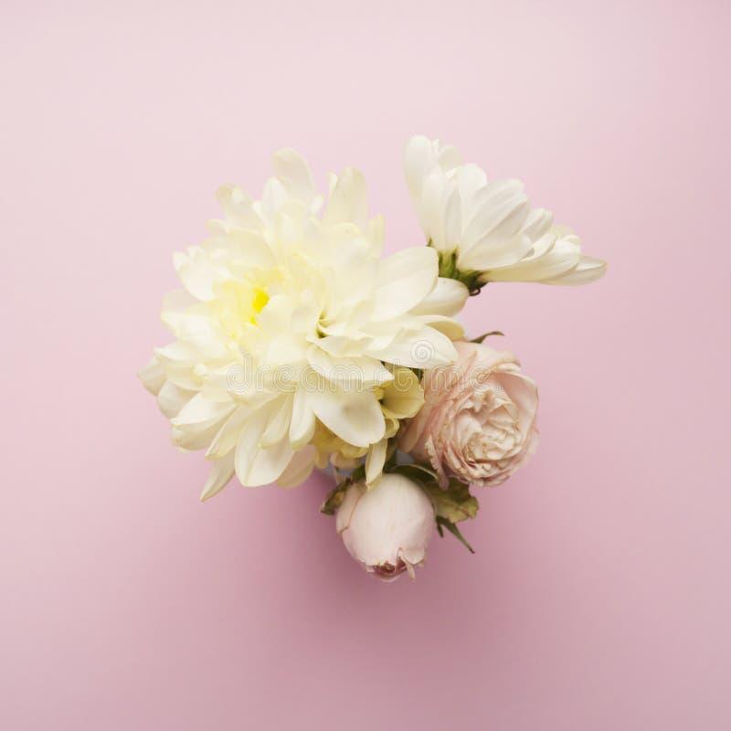 Ramo de crisantemos blancos y de rosas poner crema en un fondo rosado Endecha plana fotografía de archivo libre de regalías