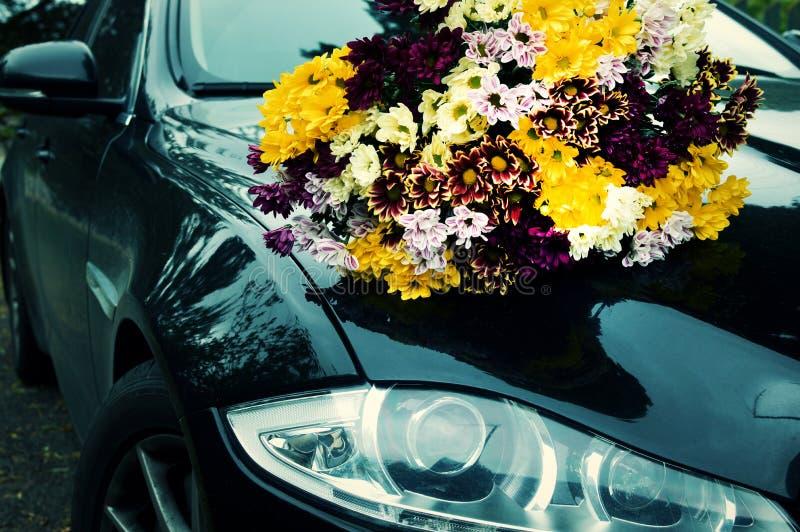 Ramo de crisantemos del color en el coche negro foto de archivo libre de regalías