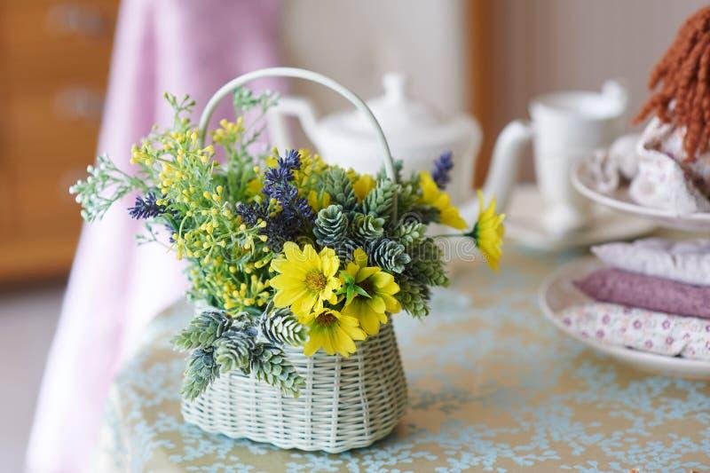 Ramo de flores amarillas en una cesta de mimbre blanca que se coloca en la tabla de madera imagen de archivo libre de regalías