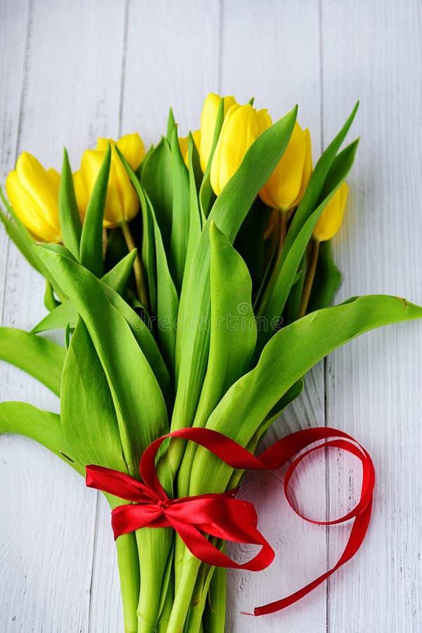 Ramo de flores amarillas de los tulipanes en el fondo de madera blanco Para primavera que espera Tarjeta de pascua feliz, el día  imagen de archivo