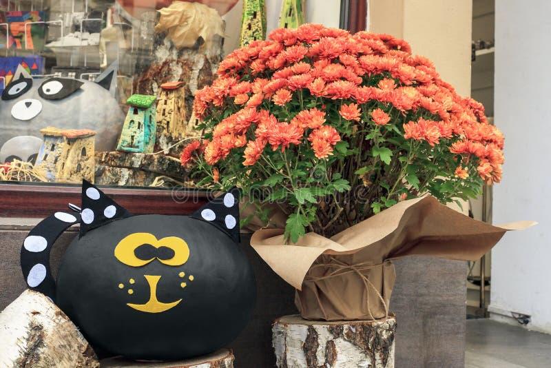 Ramo de flores anaranjadas de los crisantemos y de gato negro de los juguetes fotos de archivo libres de regalías