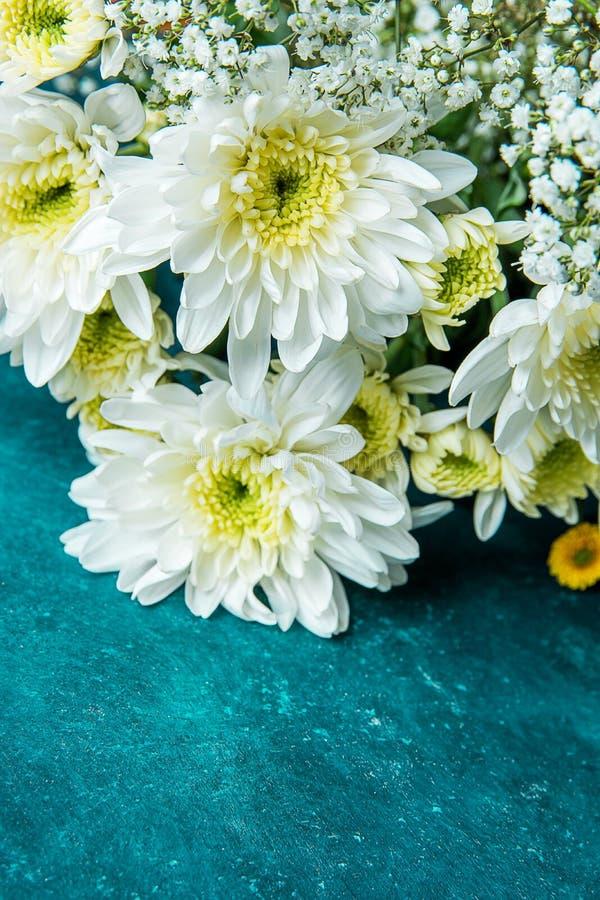 Ramo de flores blancas y amarillas del Gypsophila de la respiración del bebé de las margaritas en fondo de la turquesa de la acua fotos de archivo
