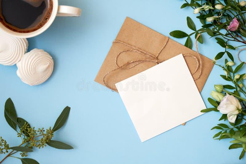 Ramo de flores, caja de regalo, cinta, sobre del arte, tarjeta de felicitación en blanco en fondo azul con el espacio de la copia fotografía de archivo libre de regalías