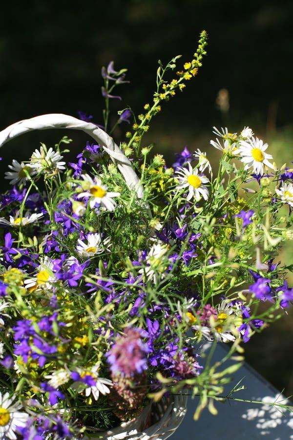 Ramo de flores del prado en una cesta imagenes de archivo