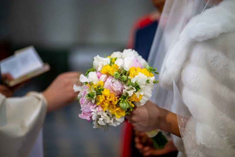 Ramo de flores en la mano de la novia durante la ceremonia de matrimonio foto de archivo libre de regalías
