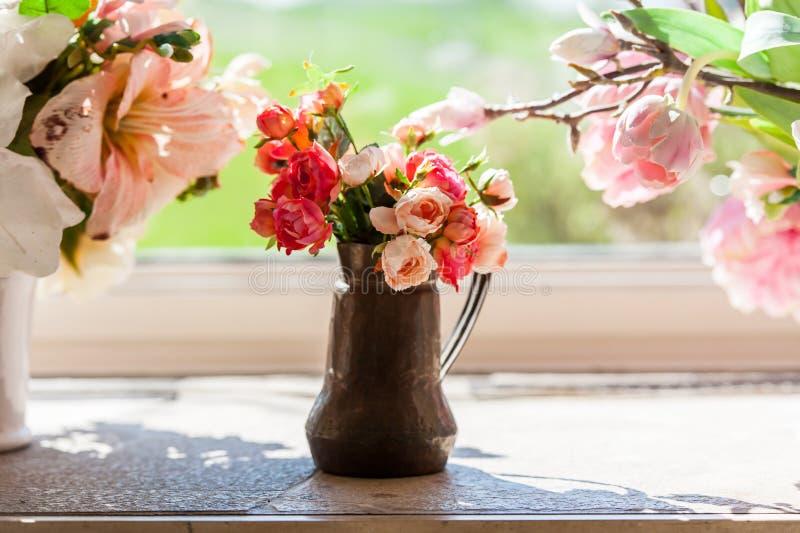 Ramo de flores en un florero delante de la ventana foto de archivo