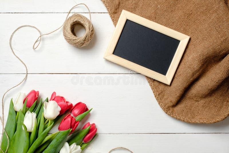 Ramo de flores de los tulipanes, marco en blanco, guita, arpillera en la tabla de madera blanca Tarjeta de felicitación del vinta imagen de archivo libre de regalías