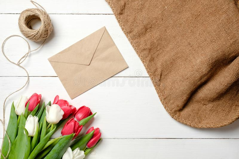 Ramo de flores de los tulipanes, sobre de Kraft, guita, arpillera en la tabla de madera blanca Tarjeta de felicitación del vintag fotografía de archivo libre de regalías