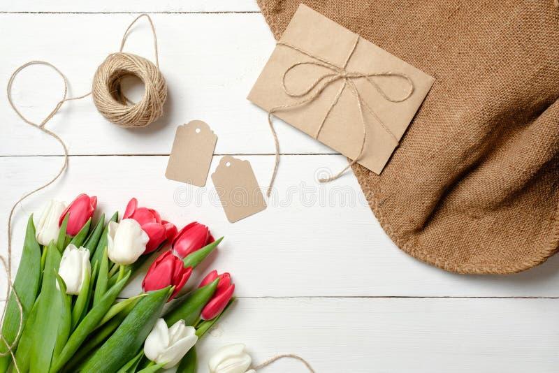 Ramo de flores de los tulipanes, sobre de Kraft, guita, etiquetas, arpillera en la tabla de madera blanca Tarjeta de felicitación fotografía de archivo libre de regalías
