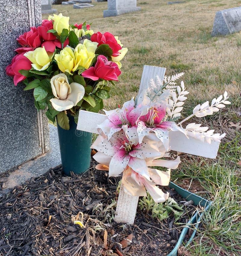 Ramo de flores y de cruz blanca en un cementerio foto de archivo